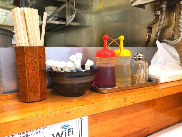カウンターに並ぶ割りばしとレンゲと調味料類