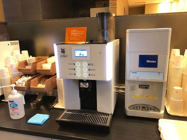 コンフォートホテル仙台西口のライブラリーカフェ内にあるコーヒーマシンと水