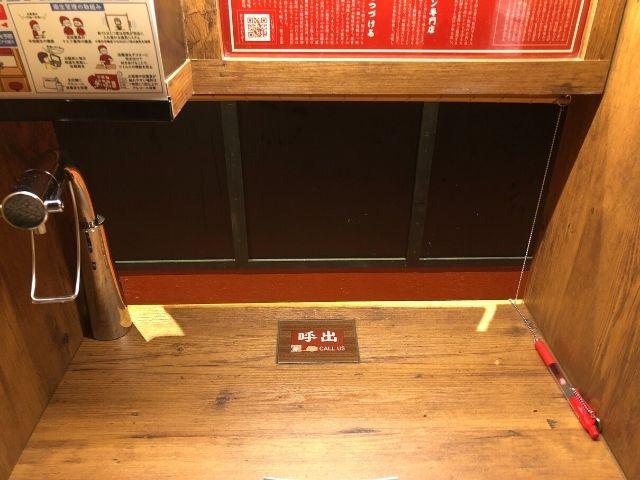 一蘭仙台駅前店のカウンターにある呼び出しボタンとセルフサービスの水