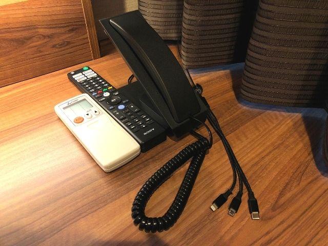 フロントへ繋がる受話器とエアコン・テレビのリモコン